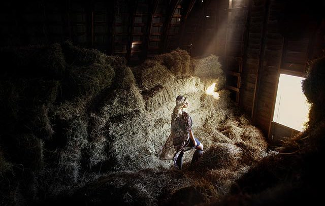 Stylized commercial photograph of a model in a barn