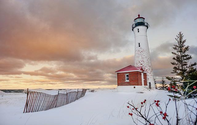advertising leisure and travel photograph of a lighthouse in winter on lake michigan