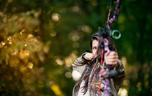 advertising image of a female archer aiming a bow and arrow during hunting