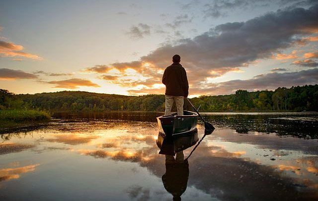 Lifestyle photograph of a man in a boat on Michigan lake